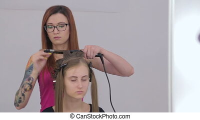 2 shots. Professional hairdresser doing hairstyle for pretty...