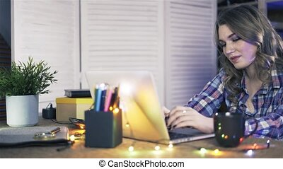 Pan shot of attractive young woman working on a laptop at office.