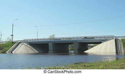 Cars going on bridge over small river on sunny day -...