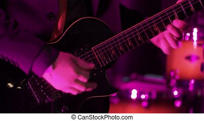Man playing guitar in nightclub shot