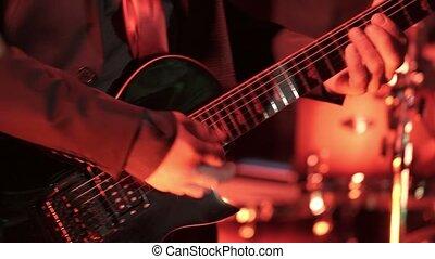 Man playing guitar in nightclub shot