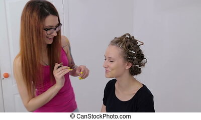 Professional make-up artist applying cream base eyeshadow primer to model eye