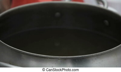 Boiling water in pot above the fire. Close up - Boiling...