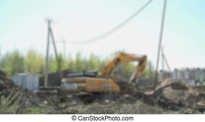 Yellow tractor digging soil on sunny day