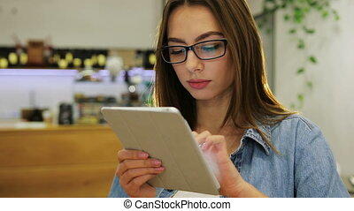 Young attractive woman using tablet touch screen and in modern cafe