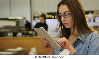 Young beautiful woman in glasses using tablet touch screen and serching for information in modern cafe
