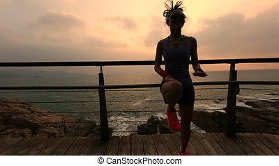 young fitness woman runner jumping on sunrise seaside