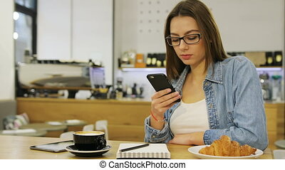 Young beautiful woman using mobile phone, texting massege,...