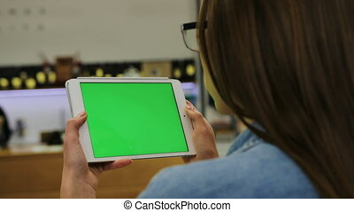 Young attractive woman in glasses watching video on tablet with green screen in the cafe. Close-up. Chroma key. Greenscreen