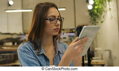 Beautiful young woman in glasses and blue shirt using tablet...