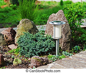 Solar-powered lamp on garden background. Selective focus.
