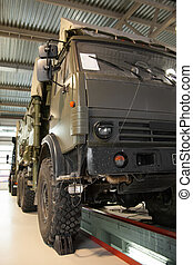 Large military truck in the service station for repair