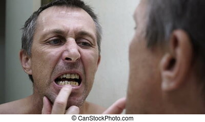 Man Looking into Mirror Inspecting Teeth Handheld - Close up...