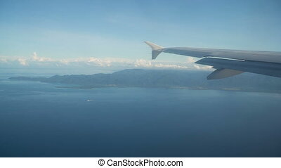 View from an airplane window on the mountains and ocean.