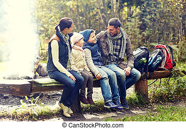 happy family sitting on bench and talking at camp - camping,...
