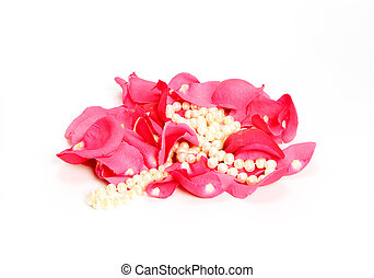 pearl beads among rose petals on white background