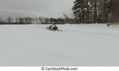 Racing on a snowmobile. - Man driving snowmobile in...