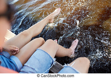 legs of young couple sitting on river berth - holidays,...