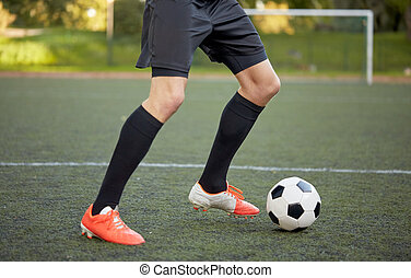 soccer player playing with ball on football field - sport,...
