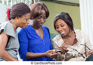 group of young women looking at the screen of a mobile...