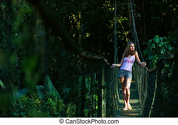 The girl on the pendant bridge in wood. The beautiful young...