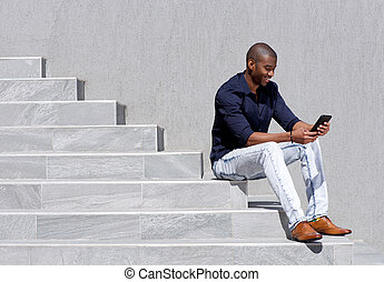 young african american man sitting on steps using tablet -...