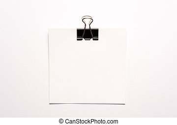 White note paper and black paperclip