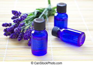 Aromatherapy oil in bottles with fresh lavenders