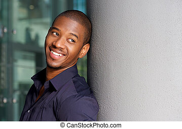 smiling black man leaning against wall outside
