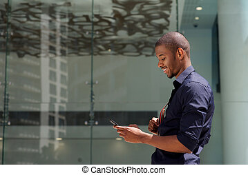 smiling black man walking outside with cellphone