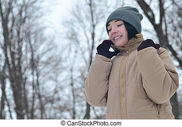 Winter portrait of young girl with smartphone - Pretty young...