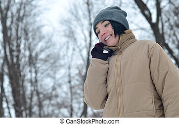 Winter portrait of young girl with smartphone - Beauty girl...