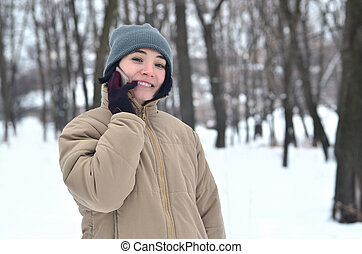 Winter portrait of young girl with smartphone - Portrait of...