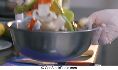 Close up hand in glove mixes vegetable in a bowl. Slowly -...