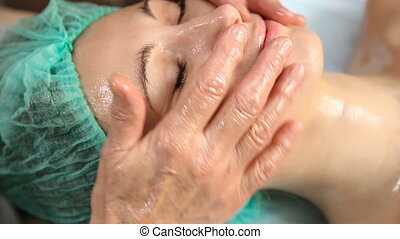 Woman doing facial massage - cosmetologist doing facial...