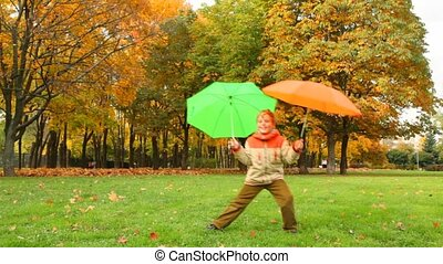 dancing boy with two umbrellas in autumn park