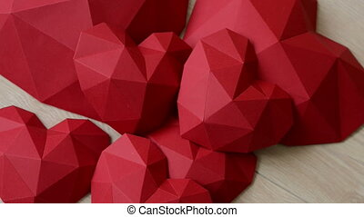 Three red polygonal paper heart shape over wooden bachground...