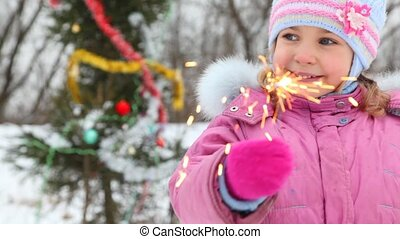 Smiling girl with sparkler against christmas tree - smiling...