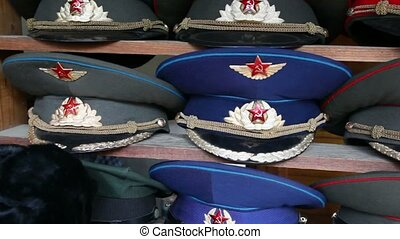 Many souvenir military caps with Soviet and Russian symbols...