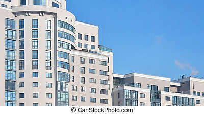 Multi-story office building with blue sky - Multi-story...