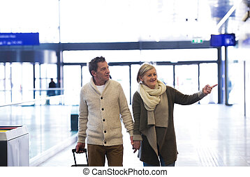 Senior couple in hallway of subway pulling trolley luggage....