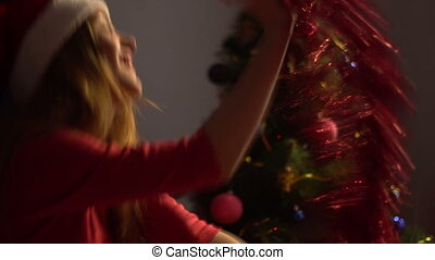 happy young woman in santa hat dancing with tinsel in hands....