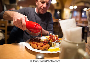 Senior man in restaurant puts ketchup on fries and schnitzel...