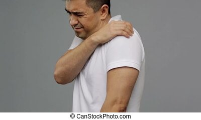 unhappy man suffering from pain in shoulder