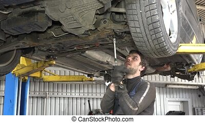 Male auto mechanic with spanner working under car in garage...