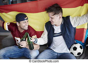 Two friends enjoying soccer on television