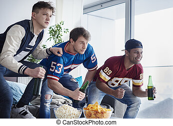 Eager sports fans on the living room