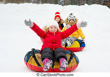 Kids on snow tubes downhill at winter day. Forest on the...