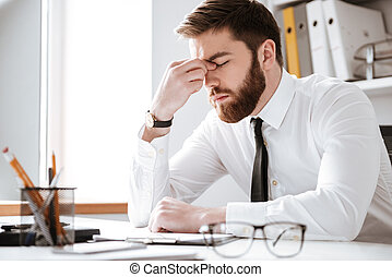 Bored young businessman sitting in office - Photo of bored...