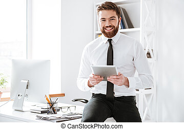 Businessman sitting in office while holding tablet . - Image...